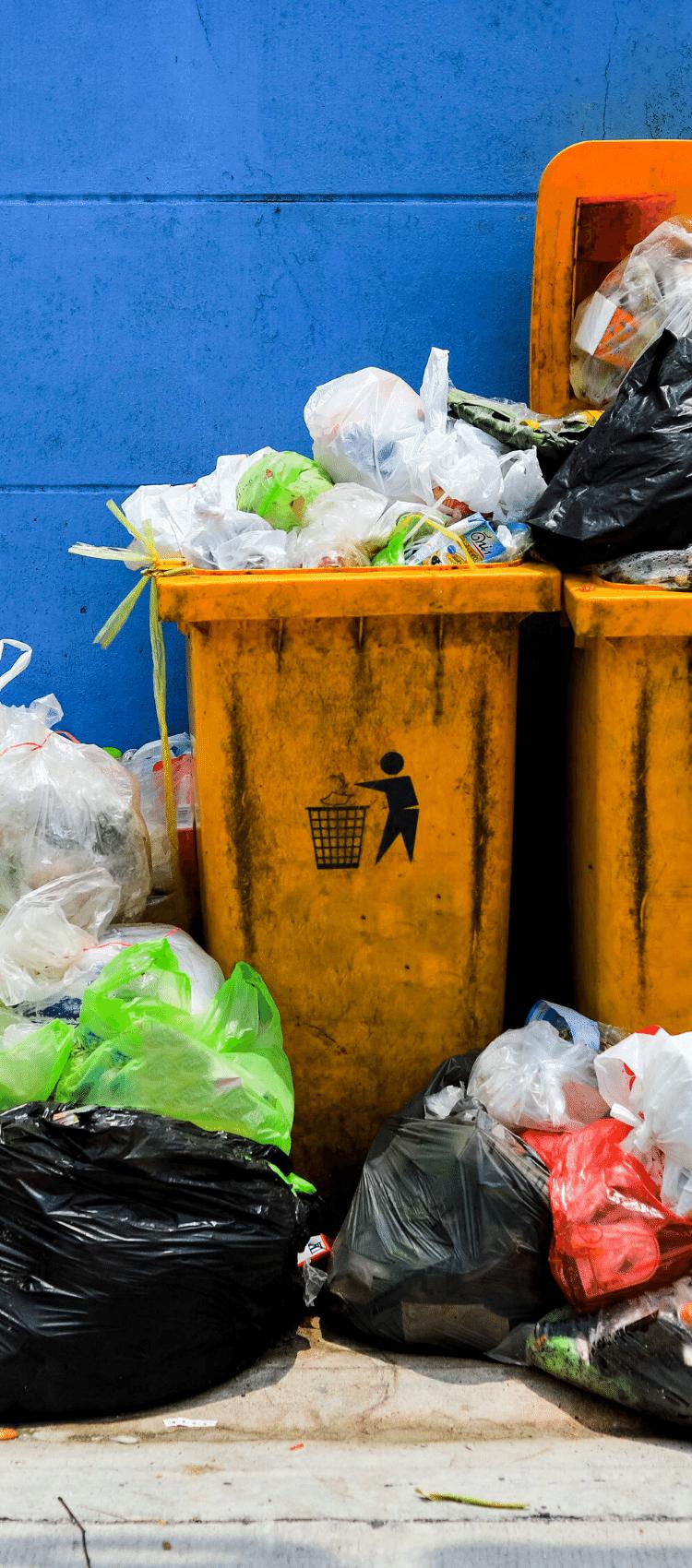 Two yellow bins fullof rubbish
